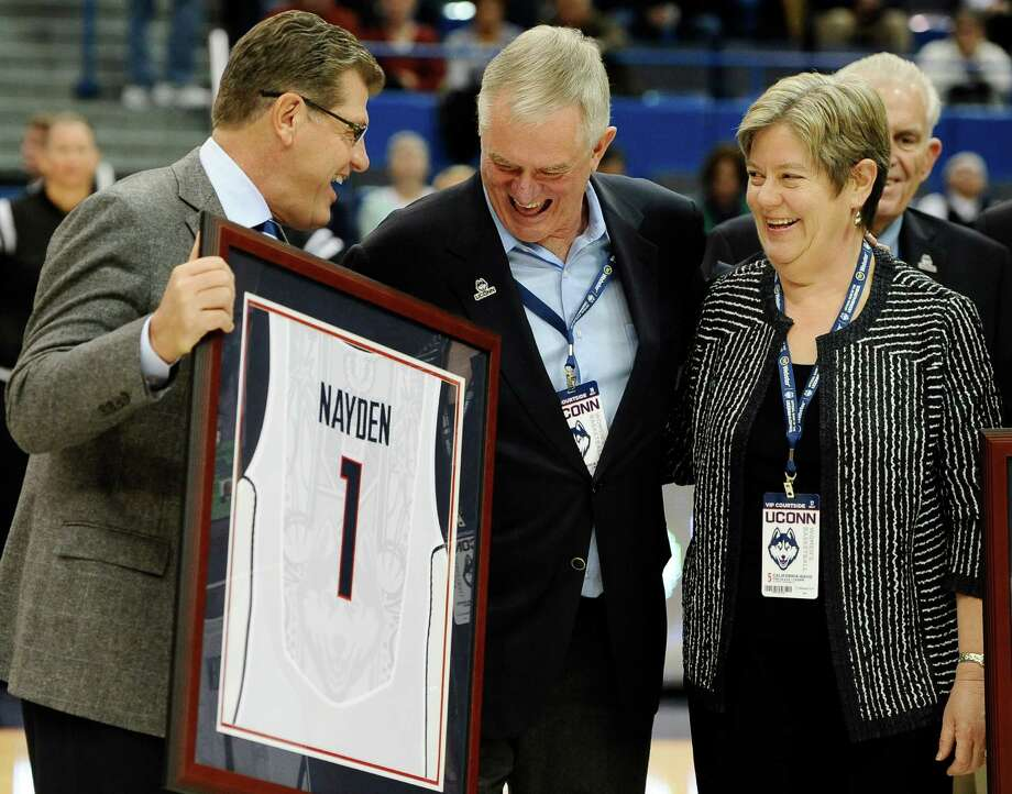 Connecticut head coach Geno Auriemma, left, presents Denis and Britta Nayden with a team jersey before an NCAA college basketball game against UC Davis, Thursday, Dec. 5, 2013, in Hartford, Conn. The Naydens, UConn alumni, have donated $3 million toward the new UConn Basketball Champions Center and for scholarships for student athletes. Photo: Jessica Hill, AP / Associated Press
