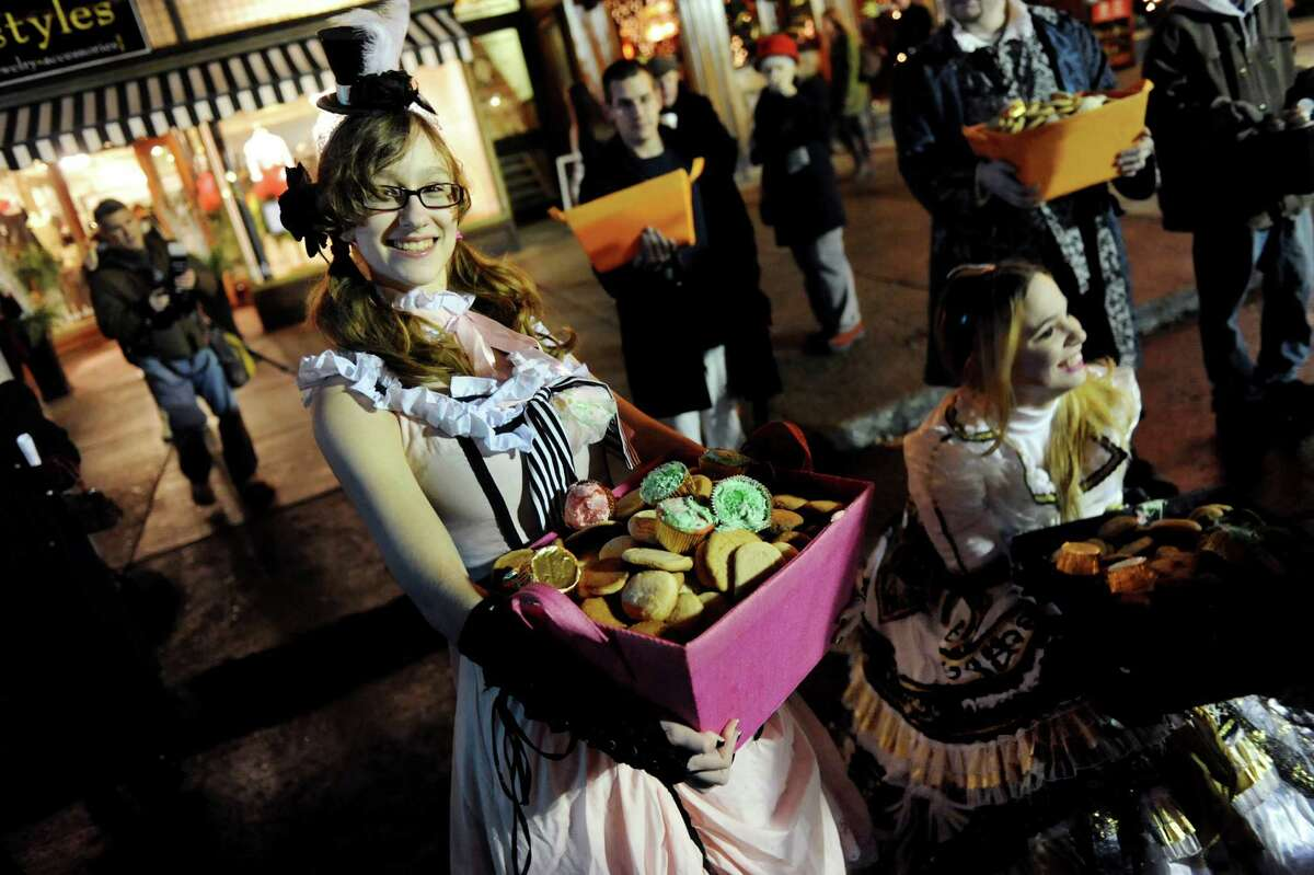 Morgan Minnolera, 17, left, and Heather Freitag, 24, both of South Glens Falls, hand out free cookies and cupcakes during the Victorian Streetwalk on Thursday, Dec. 5, 2013, in Saratoga Springs, N.Y. (Cindy Schultz / Times Union)