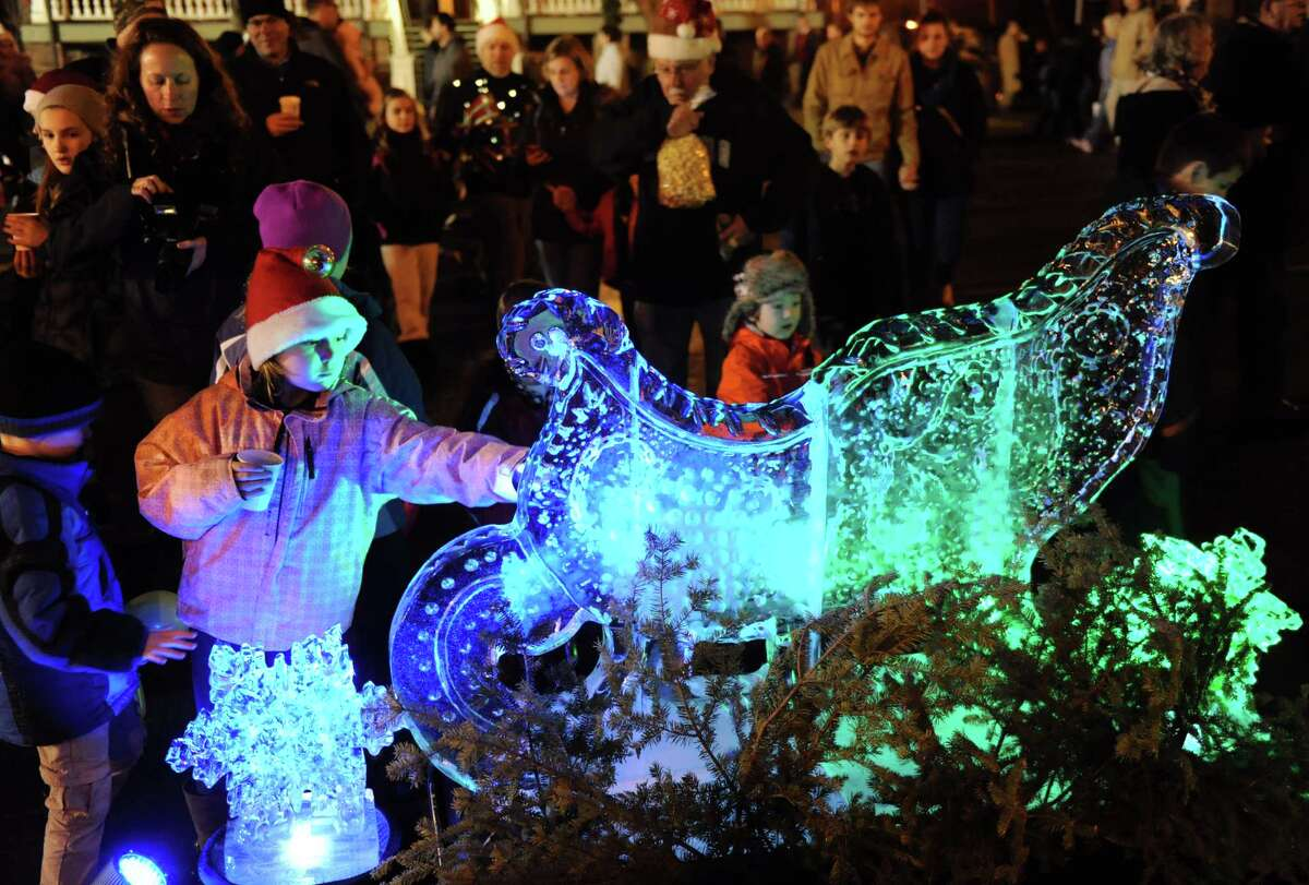 Mackenzie Dahl, 9, of Malta, left, touches the ice sculpture on display during the Victorian Streetwalk on Thursday, Dec. 5, 2013, in Saratoga Springs, N.Y. (Cindy Schultz / Times Union)