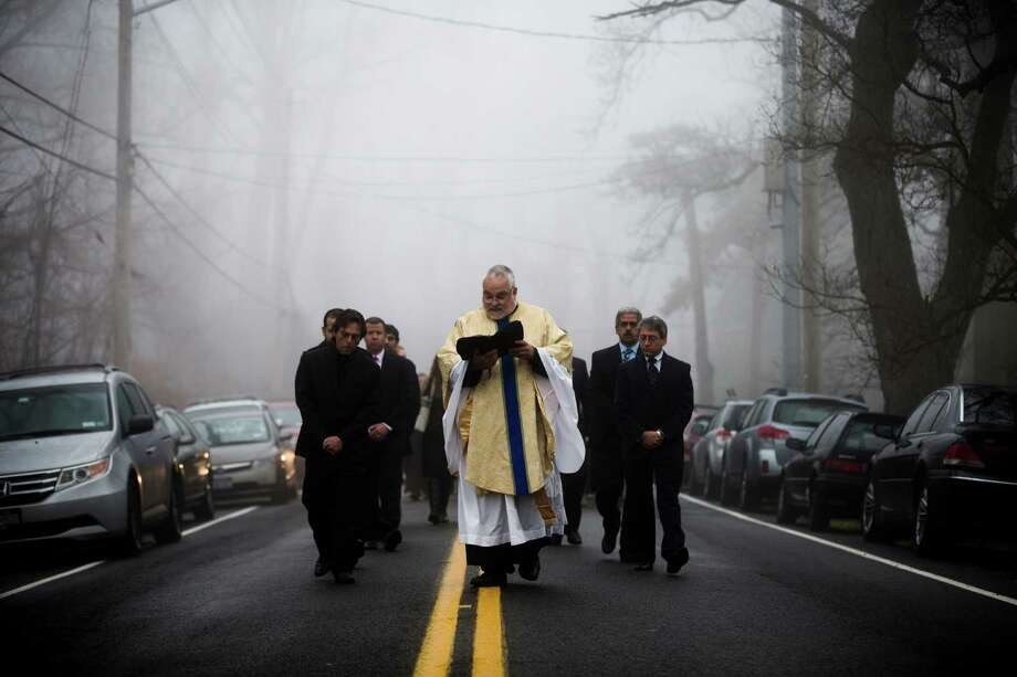 Father Eric Consentino and mourners follow a hearse carrying the casket of James Ferrari from the Church of the Divine Love towards his grave plot, Thursday, Dec. 5, 2013, in Montrose. Ferrari, 59, was killed along with three others when a speeding Metro-North Railroad train on the Hudson Line derailed in New York City. (AP Photo/John Minchillo) ORG XMIT: NYJM110 Photo: John Minchillo / FR170537 AP