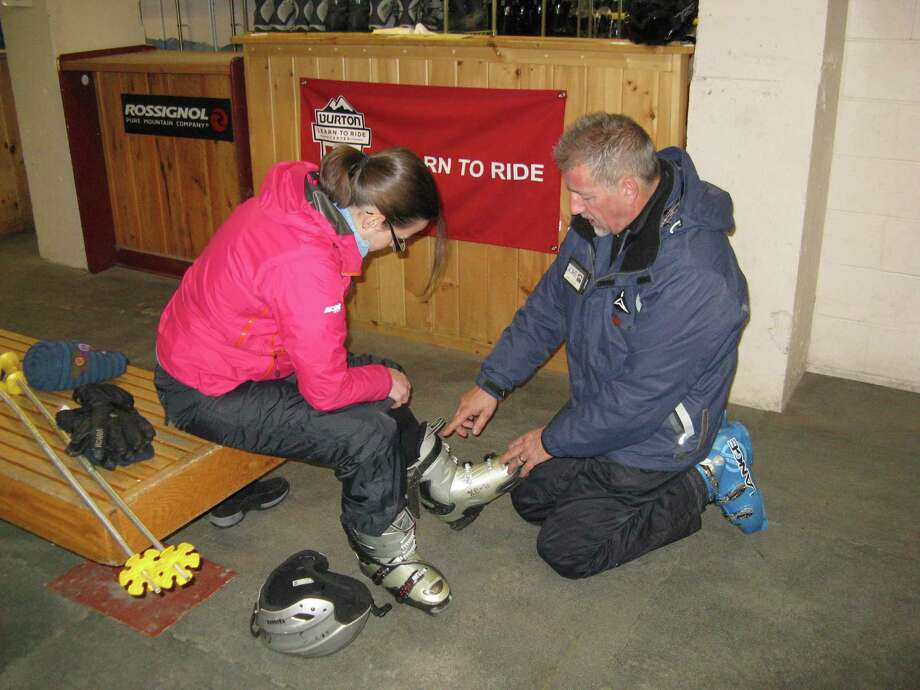 Photo by Herb Terns. Gore Mountain ski instructor Joe Childs explains downhill ski boots to outdoors writer Gillian Scott.