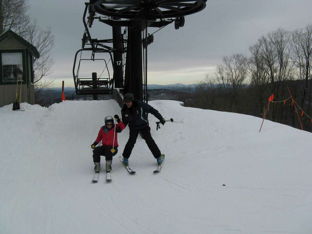 Gore Mountain ski instructor Joe Childs helps outdoors writer Gillian Scott off the chairlift.