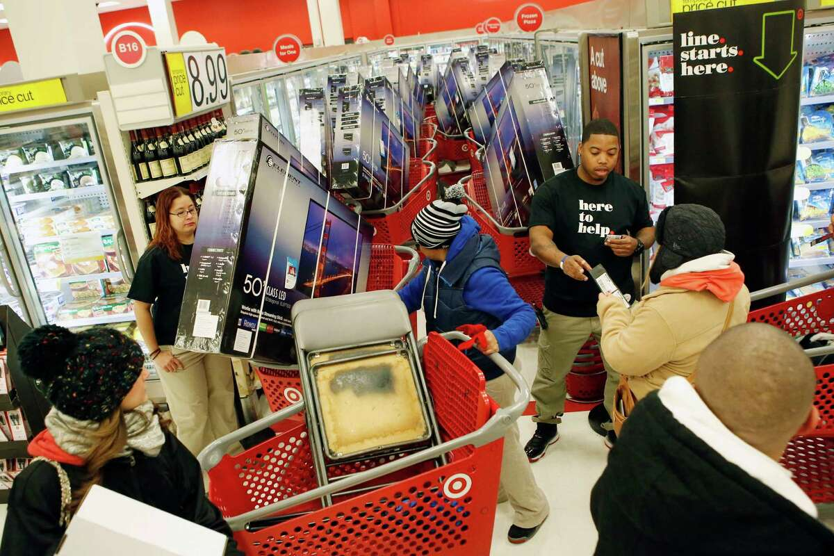 Employees assist customers at a Target store in Chicago. The U.S. economy grew at a 3.6 percent annual rate from July through September, the government said.