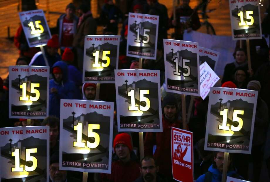 People gather at Seattle City Hall during a rally and march to make $15 the minimum wage in Seattle. The marchers started in SeaTac, the city where a voter initiative to pay workers a minimum of $15 per hour just passed. Photographed on Thursday, December 5, 2013.  (Joshua Trujillo, seattlepi.com) Photo: JOSHUA TRUJILLO, SEATTLEPI.COM