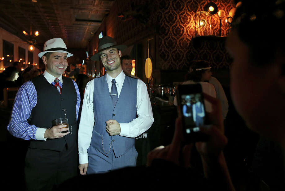 Adam Neveu (left) and Brian McCauley are photographed by Krystle Stone during The Esquire Tavern 80th birthday celebration, that coincides with the date Prohibition ended Ñ Dec. 5, 1933 Ñ known as national Repeal Day, Dec. 5, 2013. Photo: Edward A. Ornelas, San Antonio Express-News / © 2013 San Antonio Express-News