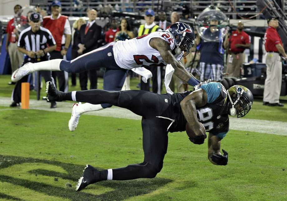 Jacksonville Jaguars tight end Marcedes Lewis (89) pulls in a one-yard touchdown reception in front of Houston Texans cornerback Kareem Jackson (25) during the first quarter of an NFL football game Thursday, Dec. 5, 2013, in Jacksonville, Fla. (AP Photo/Chris O'Meara) ORG XMIT: JVS201 Photo: Chris O'Meara / AP