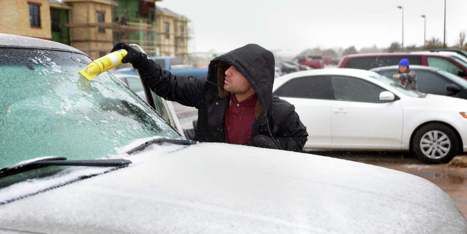 George Lara, a graduate student at the University of Texas, uses a deicer to clear the windshield of his car on Thursday, Dec. 5, 2013, in Odessa, Texas. The winter storm brought sleet and freezing to the West Texas region on Thursday, coating roads with a layer of thin ice and prompting many truckers to pull off the interstate. Photo: Mark Sterkel, AP / The Odessa American