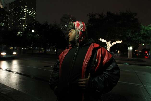 Aaron Hailey is warmly dressed as he waits for the METRO bus in downtown on Dec. 6, 2013. Temperatures are in the low 40s and are expected to keep dropping into the low 30s. Photo: Mayra Beltran, Houston Chronicle