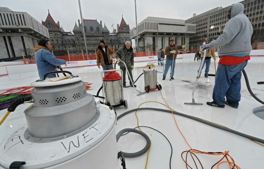 Members of OGS and local 190 clean up melted ice on the Empire State Plaza ice rink on Thursday, Dec. 5, 2013 in Albany, N.Y. The logos on the ice were smeared so they had to be scraped up and will need to be redone. (Lori Van Buren / Times Union archive) Photo: Lori Van Buren