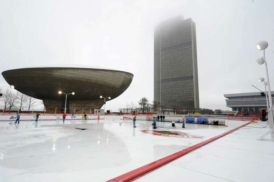 The Corning Tower is partly covered in fog as mostly OGS workers clean up melted ice on the Empire State Plaza ice rink on Thursday, Dec. 5, 2013 in Albany, N.Y. The logos on the ice were smeared so they had to be scraped up and will need to be redone. (Lori Van Buren / Times Union archive) Photo: Lori Van Buren