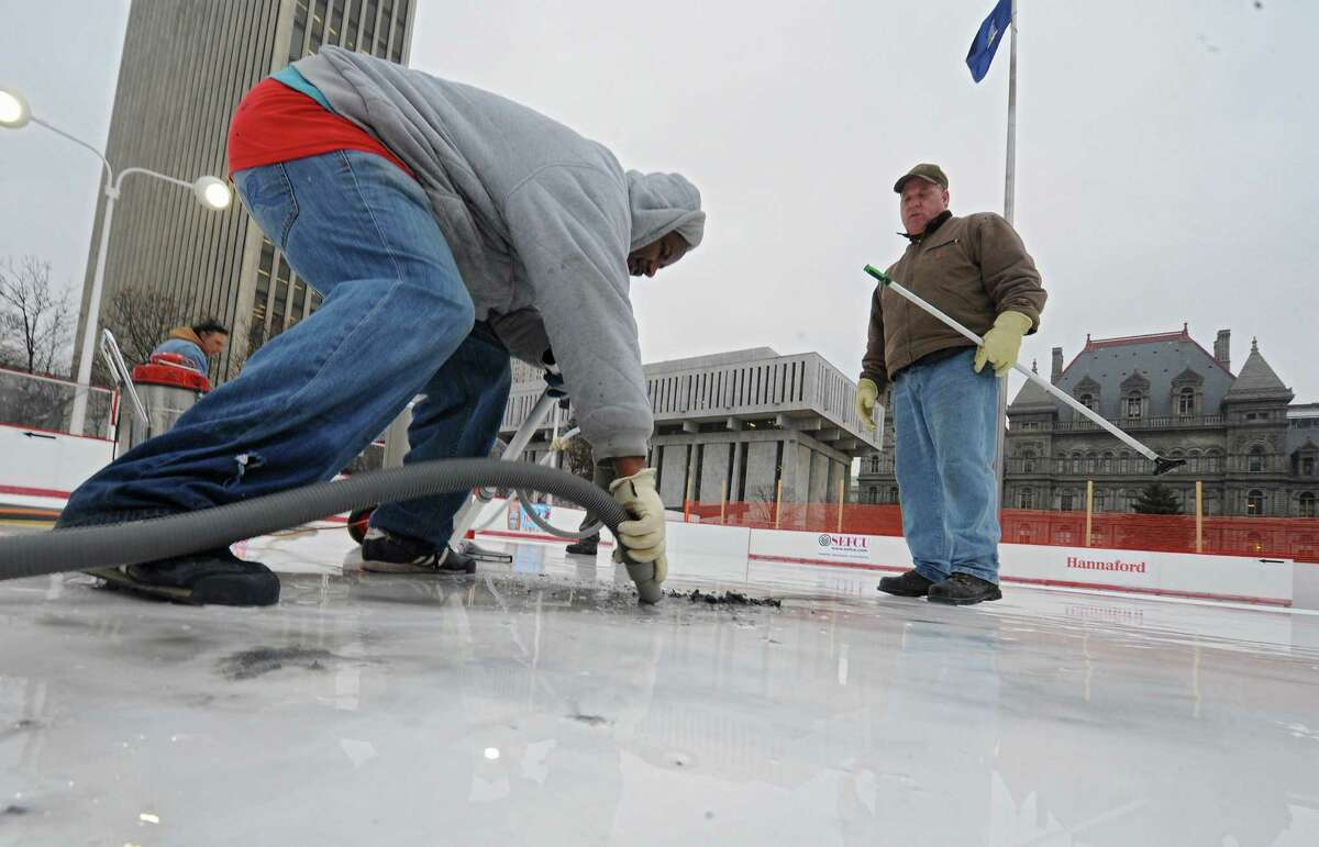 Charles Robinson of Local 190, left, uses a shop vac on a scraped up logo in the melted ice of the Empire State Plaza ice rink as Arnold Buell of OGS, right, looks on Thursday, Dec. 5, 2013 in Albany, N.Y. The logos on the ice were smeared so they had to be scraped up and will need to be redone. (Lori Van Buren / Times Union archive)