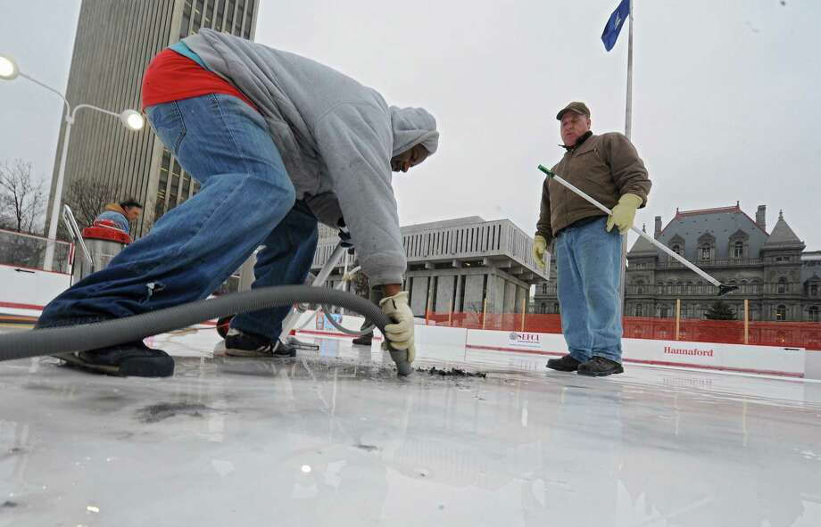 Charles Robinson of Local 190, left, uses a shop vac on a scraped up logo in the melted ice of the Empire State Plaza ice rink as Arnold Buell of OGS, right, looks on Thursday, Dec. 5, 2013 in Albany, N.Y. The logos on the ice were smeared so they had to be scraped up and will need to be redone. (Lori Van Buren / Times Union archive) Photo: Lori Van Buren