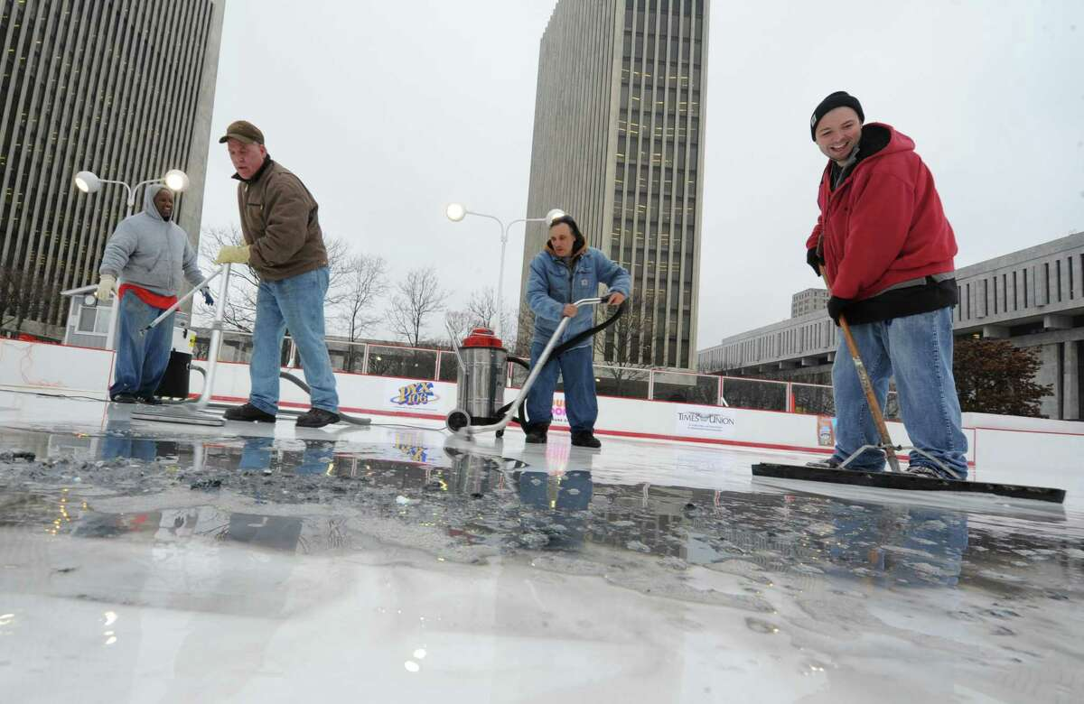 From left, Charles Robinson of Local 190, Arnold Buell of OGS, Paul Spardarn of OGS and Joel Muller of OGS clean up melted ice on the Empire State Plaza ice rink on Thursday, Dec. 5, 2013 in Albany, N.Y. The logos on the ice were smeared so they had to be scraped up and will need to be redone. (Lori Van Buren / Times Union archive)
