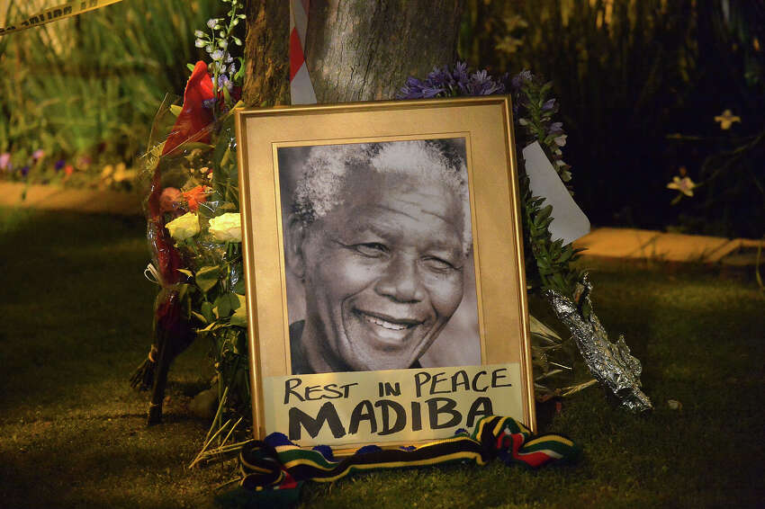 This picture shows a framed image of former South African president Nelson Mandela as people pay tributes following his death, in Johannesburg on December 6, 2013. Nelson Mandela, the revered icon of South Africa's anti-apartheid struggle and a towering figure of 20th century politics, died on December 5 aged 95.