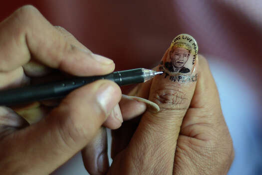 An Indian artist draws a miniature portrait of South African former president Nelson Mandela onto his thumbnail as a part of his homage in Siliguri on December 6, 2013. Mandela, the revered icon of the anti-apartheid struggle in South Africa and one of the towering political figures of the 20th century, has died aged 95. Mandela, who was elected South Africa's first black president after spending nearly three decades in prison, had been receiving treatment for a lung infection at his Johannesburg home since September, after three months in hospital in a critical state. Photo: DIPTENDU DUTTA, AFP/Getty Images / 2013 AFP