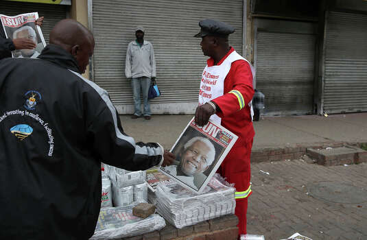 A man sells newspapers carrying the news on December 6, 2013, in Johannesburg, South Africa. The Father of the Nation, Nelson Mandela, Tata Madiba, passed away quietly on the evening of December 5, 2013 at his home in Houghton with family. Photo: Sunday Times, Getty Images / 2013 Gallo Images (PTY) LTD