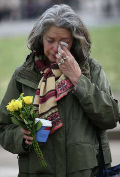 Joanna Vignola weeps before placing a floral tribute at the foot of a statue to Nelson Mandela in Parliament Square on December 6, 2013 in London, England. Mandela was a leader that helped conquer apartheid in racially divided South Africa after being jailed for his activism for decades. He was South Africa's first black president. He died yesterday at the age of 95. Photo: Peter Macdiarmid, Getty Images / 2013 Getty Images