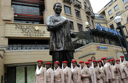 Cabin crew members pose on December 6, 2013 in front of a statue of late South African President Nelson Mandela in Johannesburg, a day after his death. Mandela, the revered icon of the anti-apartheid struggle in South Africa and one of the towering political figures of the 20th century, has died aged 95. Mandela, who was elected South Africa's first black president after spending nearly three decades in prison, had been receiving treatment for a lung infection at his Johannesburg home since September, after three months in hospital in a critical state. Photo: STEPHANE DE SAKUTIN, AFP/Getty Images / 2013 AFP