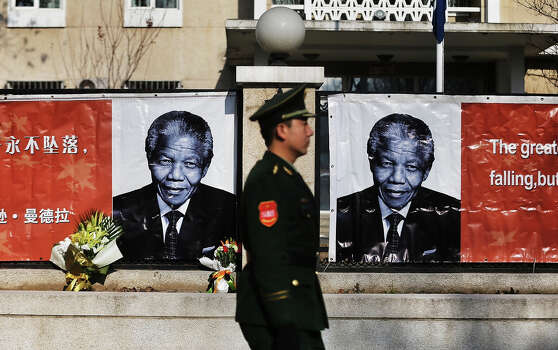 A Chinese security officer walks past images of former South African president Nelson Mandela at the Embassy of South Africa on December 6, 2013 in Beijing, China. Mandela was a leader that helped conquer apartheid in racially divided South Africa after being jailed for his activism for decades. He was South Africa's first black president. He died yesterday at the age of 95. Photo: ChinaFotoPress, ChinaFotoPress Via Getty Images / 2013 ChinaFotoPress