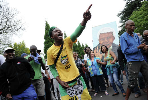 A man wearing a yellow t-shirt of the South African ANC ruling party grieves with other people on December 6, 2013 outside the house of former South African President Nelson Mandela in Johannesburg. Mandela, the revered icon of the anti-apartheid struggle in South Africa and one of the towering political figures of the 20th century, has died aged 95. Mandela, who was elected South Africa's first black president after spending nearly three decades in prison, had been receiving treatment for a lung infection at his Johannesburg home since September, after three months in hospital in a critical state. Photo: STEPHANE DE SAKUTIN, AFP/Getty Images / 2013 AFP