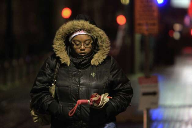 """""""I didn't expect it to be this warm"""" says Sheila Duncan, 28, as she walks through downtown in the early morning with temp"""