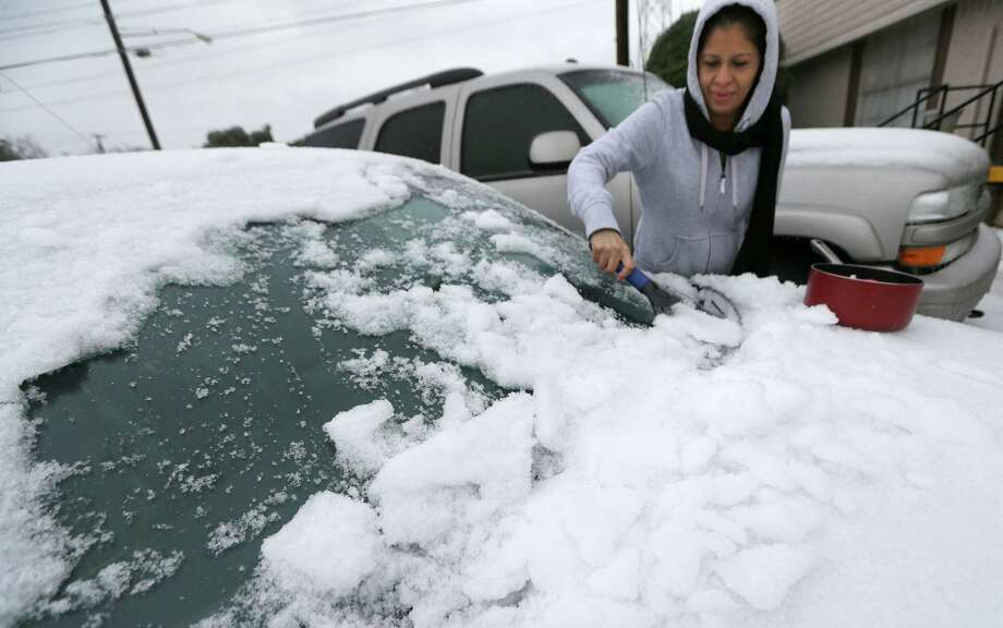 Laura Perez scrapes ice off of her car as she prepares to drive to work in icy conditions Friday morning, Dec. 6, 2013, in Dallas.  An ice storm in North Texas has knocked out power to more than a quarter of a million homes and business, canceled almost 1,000 flights and contributed to a fatal wreck. The National Weather Service issued a winter storm warning for the Dallas area until Friday night. (AP Photo/LM Otero) Photo: LM Otero, Associated Press / AP