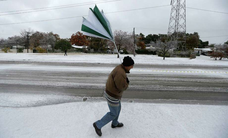 A gust of wind collapses Joseph Mezo's umbrella as he walks to work in light sleet  and ice conditions Friday morning, Dec. 6, 2013, in Dallas.  Winter storm and ice warnings are in effect through much of today for parts of six states in the Midwest, including Texas, Missouri, Illinois and Indiana. (AP Photo/LM Otero) Photo: LM Otero, Associated Press / AP