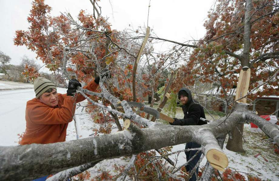 Kenny Burger, left, helps his father Harold Burger saw tree ice covered tree limbs knocked down by a winter storm Friday morning, Dec. 6, 2013, in Richardson, Texas.  Winter storm and ice warnings are in effect through much of today for parts of six states in the Midwest, including Texas, Missouri, Illinois and Indiana. (AP Photo/LM Otero) Photo: LM Otero, Associated Press / AP