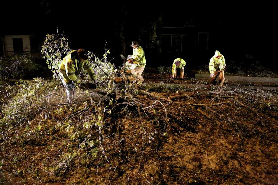 City of Paris Street Department employee's use a chain saws to cut up a large tree blocking 17th Northeast Street in Paris, Texas this morning.  A winter storm moved into North East Texas Friday, Dec. 6 2013 bringing with it freezing rain, ice and temperatures in the low 20's. (AP Photo / The Paris News: Sam Craft) Photo: Sam Craft, Associated Press / AP