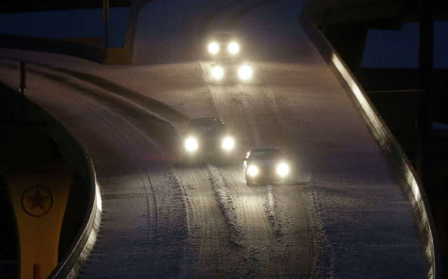 Commuters make their way on an ice covered highway early Friday morning, Dec. 6, 2013, in Dallas. An ice storm has coated north Texas in a sheet of ice causing much of the region to cancel school and other activities. (AP Photo/LM Otero) Photo: LM Otero, Associated Press / AP