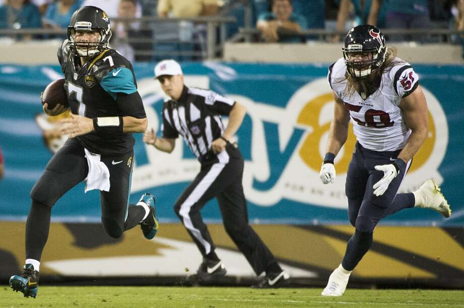 Jaguars quarterback Chad Henne (7) scrambles away from Texans outside linebacker Brooks Reed. Photo: Smiley N. Pool, Houston Chronicle