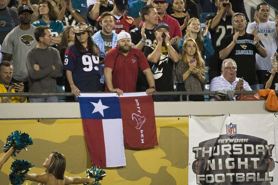 A pair of Texans fans react as Jaguars fans celebrate a defensive stop. Photo: Smiley N. Pool, Houston Chronicle