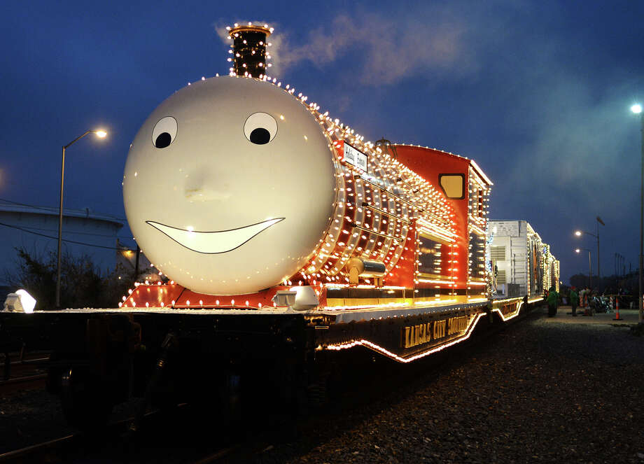 "Rudy, the smiling engine of the KCS Holiday Express, is lit by Christmas lights on Thursday night. Thousands flocked to the Kansas City Southern Holiday Express on Thursday evening, bussing to the staging area from the parking lot of the Montagne Center in order to see Santa and take in the Christmas-themed attraction. Carrying on the tradition of the ""Santa Train"" of 1997, the six-car train is in its 13th year of traveling from station to station. At each stop, the KCS Charitable Fund makes a contribution of gift cards to the local Salvation Army. Photo taken Jake Daniels/@JakeD_in_SETX Photo: Jake Daniels / ©2013 The Beaumont Enterprise/Jake Daniels"