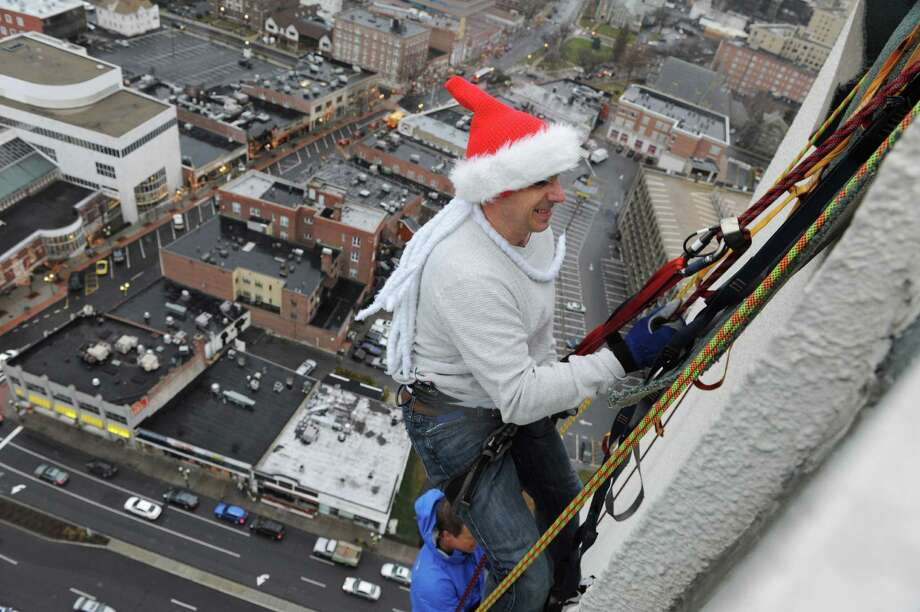 Brian Cashman, General Manager of the New York Yankees rappels from the one of Stamford, Conn's tallest buildings, The Landmark Building on Friday December 6, 2013. Photo: Dru Nadler / Stamford Advocate Freelance