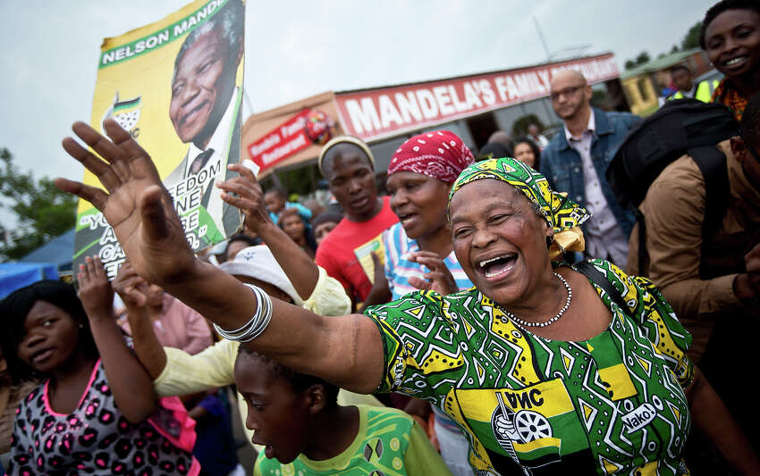 Mourners sing and dance to celebrate the life of Nelson Mandela, in the street outside his old house in Soweto, Johannesburg, South Africa, Friday, Dec. 6, 2013. Flags were lowered to half-staff and people in black townships, in upscale mostly white suburbs and in South Africa's vast rural grasslands commemorated Nelson Mandela with song, tears and prayers on Friday while pledging to adhere to the values of unity and democracy that he embodied.