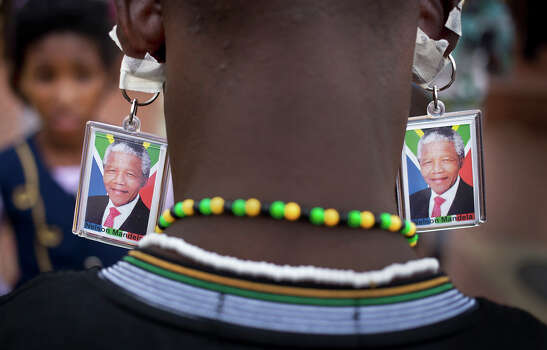 A man wears keyrings showing the face of Nelson Mandela taped to his ears to mimic earrings as he and others celebrate his life, in the street outside his old house in Soweto, Johannesburg, South Africa Friday, Dec. 6, 2013. Flags were lowered to half-staff and people in black townships, in upscale mostly white suburbs and in South Africa's vast rural grasslands commemorated Nelson Mandela with song, tears and prayers on Friday while pledging to adhere to the values of unity and democracy that he embodied. Photo: Ben Curtis, AP / AP