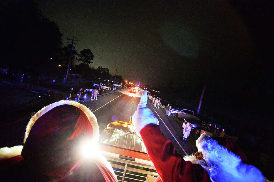 "Lumberton volunteer firefighters Julian Hernandez, right, and Becky Kelly ride on top of the Lumberton Christmas float during the 13th annual lighted night time Christmas parade ""O Holy Night in the Big Thicket""  Michael Rivera/@michaelrivera88"