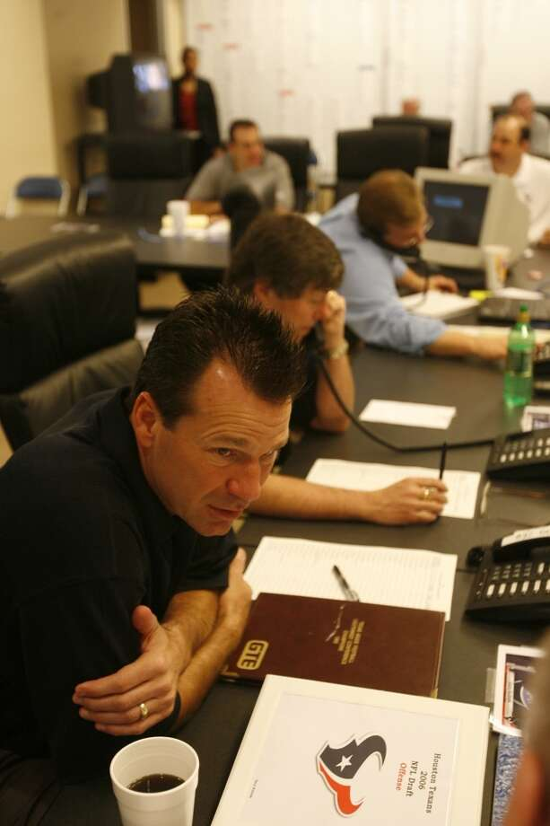 Gary Kubiak talks to assistant coach Mike Sherman, not pictured as Charley Casserly, back, talks on the phone in the Texans War room at Reliant Stadium before the 2006 NFL draft. Photo: Nick De La Torre, Houston Chronicle