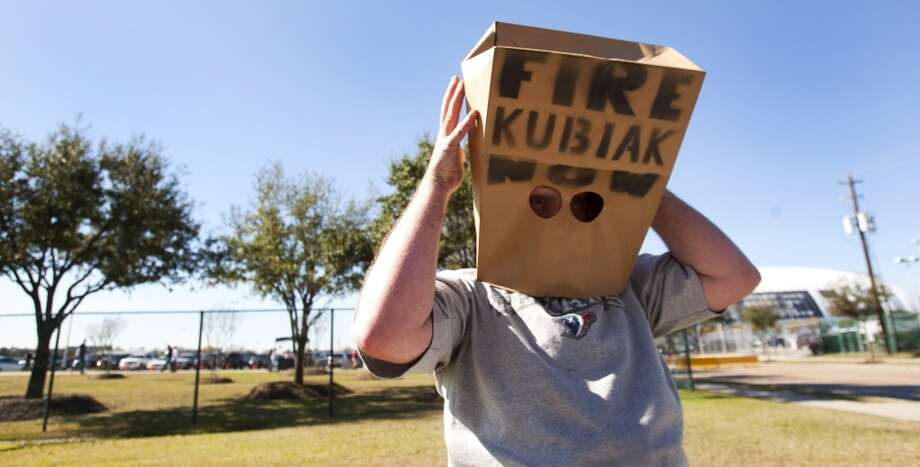 "Texans fan Kris Mitchell dons a paper bag outside Reliant Stadium before the 2010 season finale. Mitchell was one of three ""protesters"" outside the stadium calling for Texans head coach Gary Kubiak to be fired. Photo: Brett Coomer, Houston Chronicle"