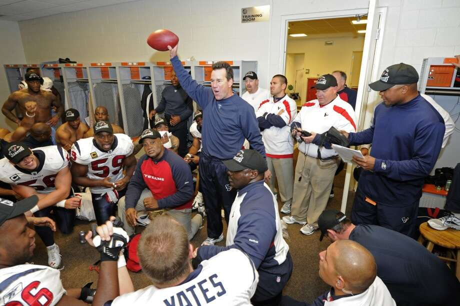 Gary Kubiak holds up a ball while talking to his players and coaches in the locker room after the win over the Bengals. Photo: Bill Baptist, Houston Texans