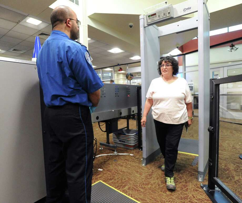 Airline passenger Martha Rubinson of San Francisco walks through security screening with her shoes on during the debut of TSA PreCheck, an expedited screening program that allows pre-approved travelers to leave on their shoes, light outerwear, belt, keep their laptop in its case and their 3-1-1 compliant liquids/gels bag in a carry-on in the designated Pre-check screening lane, at Westchester County Airport, White Plains, N.Y., Dec. 6, 2013. Photo: Bob Luckey / Greenwich Time