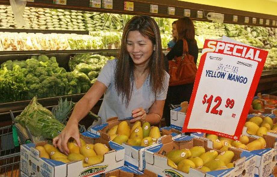 Ashley Vu shops for yellow mangoes in the Fresh Produce department at 99 Ranch Market Photo: For The Chronicle/Gary Fountain