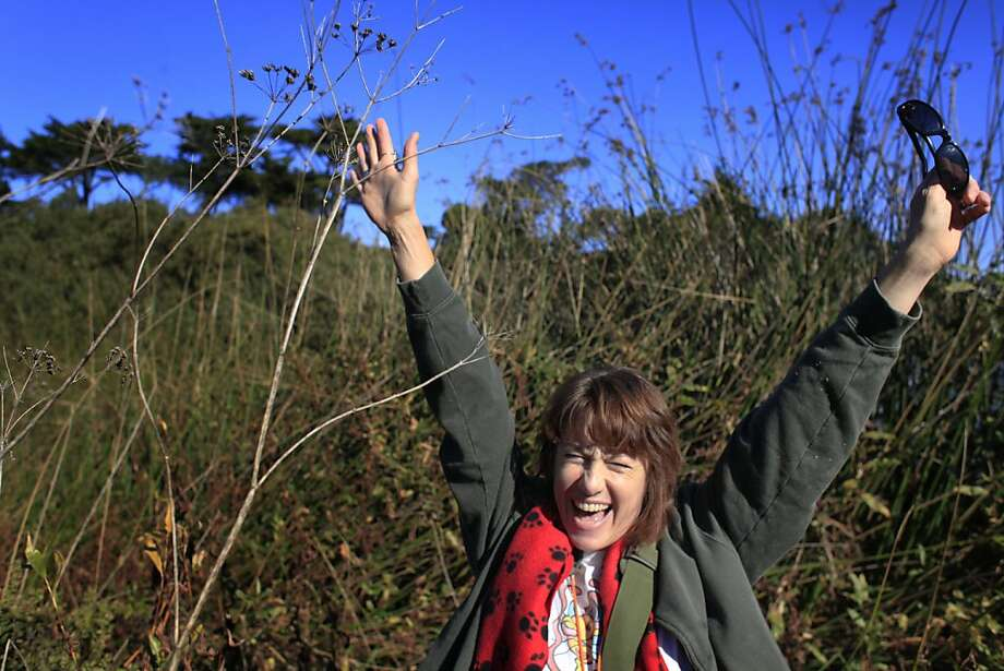 Charlotte Monte exults after finding a geocache in the bushes around San Francisco's Lake Merced. Photo: Mike Kepka, The Chronicle