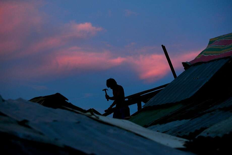 Tacloban rebuilds: A typhoon survivor constructs a frame for his destroyed house in Tacloban, Philippines' Leyte province. Photo: Noel Celis, AFP/Getty Images