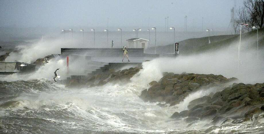 """Brave or foolish?A """"storm spotter"""" stands on the seawall in Malmo as winter storm Xaver, locally known as Sven, slams into southern Sweden. Sven killed at least one person, uprooted trees, delayed trains and left tens of thousands without power. Photo: Johan Nilsson, AFP/Getty Images"""