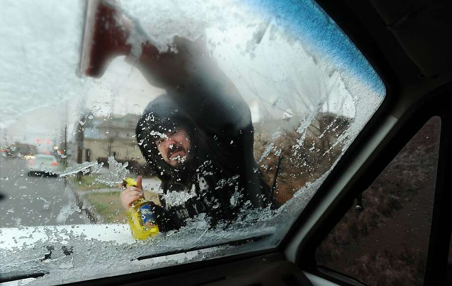 Who are you and how did you get in my car?!In Owensboro, Ky., Seth English scrapes the ice off his windshield and discovers someone with a camera in the front seat. Photo: John Dunham, Associated Press