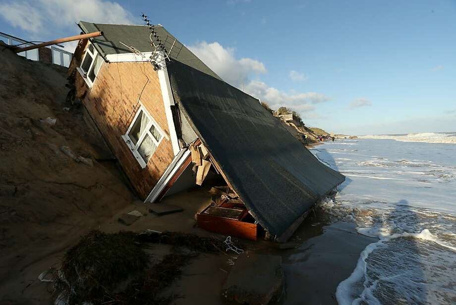 Beachfront bulldozing: This cottage in Hemsby, England, will never be the same after high water undermined its foundation, causing it to pitch into the sea. A severe winter storm and the highest tidal surge in 60 years hit Britain's east coast towns overnight, causing flooding and widespread property damage. Photo: Stephen Pond, Getty Images