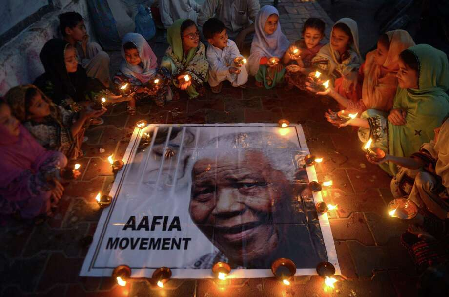 Pakistani schoolchildren hold lamps during a memorial tribute to South African  president Nelson Mandela, in Karachi on Friday.  People gathered in cities around the world to make their own personal tributes to Nelson Mandela, who died Thursday. Photo: AFP / Getty Images