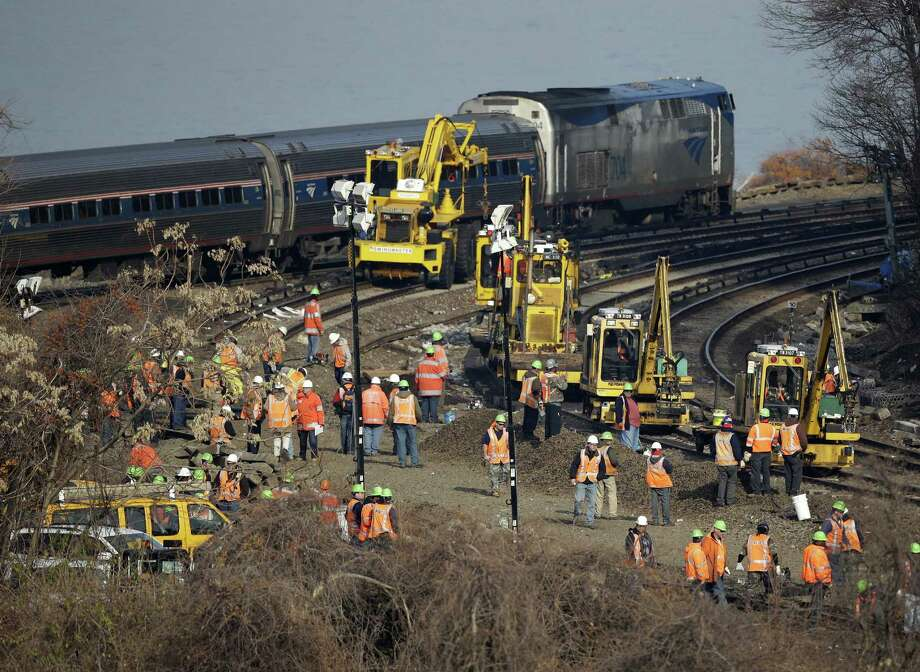 A train passes by the scene of repair efforts at the site of a train derailment in the Bronx borough of New York, Tuesday, Dec. 3, 2013.  NTSB member Earl Weener says information from the train's two data recorders shows the train was going 82 mph on a turn when it should have been going no more than 30 mph. Photo: Seth Wenig, AP Photo/Seth Wenig / Associated Press