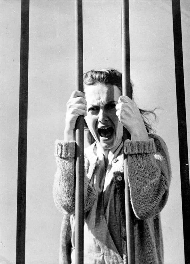 1948:  British actress Olivia De Havilland clutches the bars of her cell in the film 'The Snake Pit', about a girl who becomes deranged and experiences the horrors of a mental institution. The film was directed by Anatole Litvak for 20th Century Fox.  (Photo by Hulton Archive/Getty Images) Photo: Getty Images